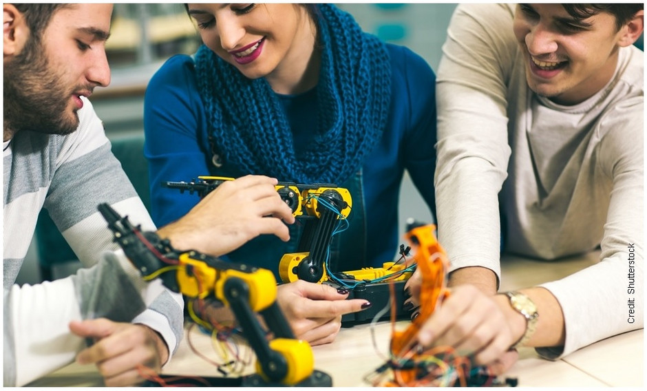 Tree students test on models of industrial robots.